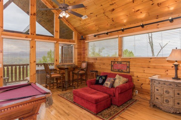 Table and two chairs, over-sized chair with ottoman, and pool table in the loft space at Howlin' in the Smokies, a 2 bedroom cabin rental located in Pigeon Forge