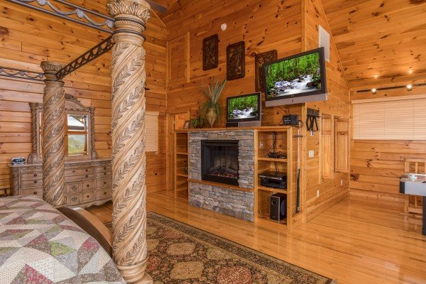 Loft room with a king canopy bed, fireplace, and two TVs at Howlin' in the Smokies, a 2 bedroom cabin rental located in Pigeon Forge