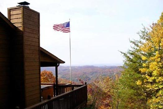 an emaerican flag hangs hight with a smoky mountain background at america's view a 2 bedroom cabin rental located in pigeon forge