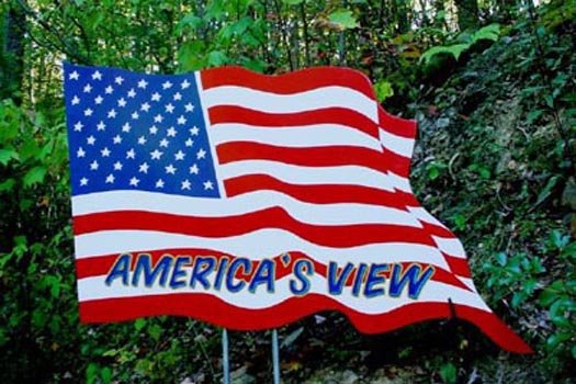 a custom american flag with cabin name signage at america's view a 2 bedroom cabin rental located in pigeon forge