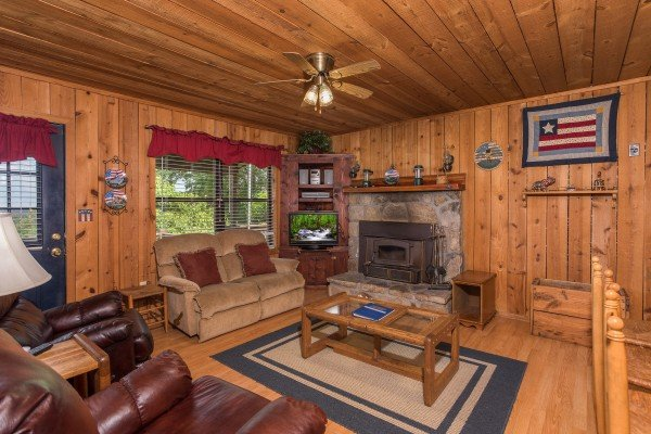 living room with wood burning fireplace at america's view a 2 bedroom cabin rental located in pigeon forge