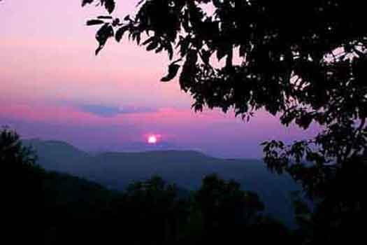 a sun setting behind the smoky mountains at america's view a 2 bedroom cabin rental located in pigeon forge