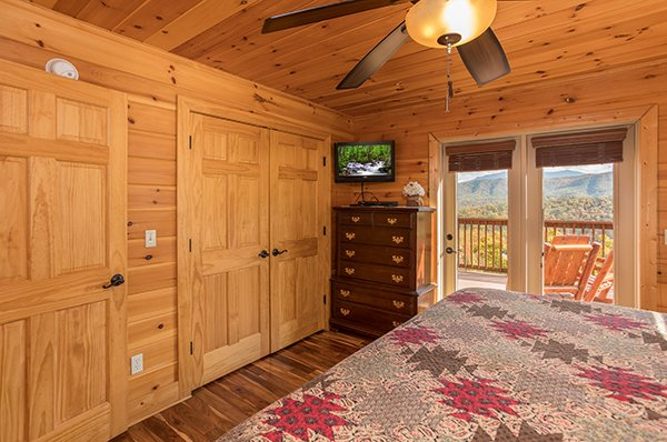 Dresser, TV, and deck access at Southern Sunrise, a 4 bedroom cabin rental located in Pigeon Forge