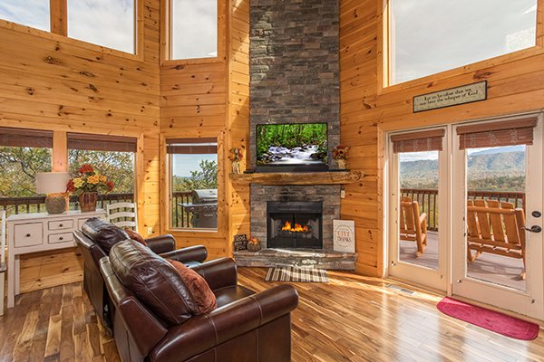 Living room with fireplace, TV, and deck access at Southern Sunrise, a 4 bedroom cabin rental located in Pigeon Forge
