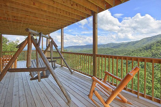 Lower level deck with swing and rockers at Southern Sunrise, a 4 bedroom cabin rental located in Pigeon Forge