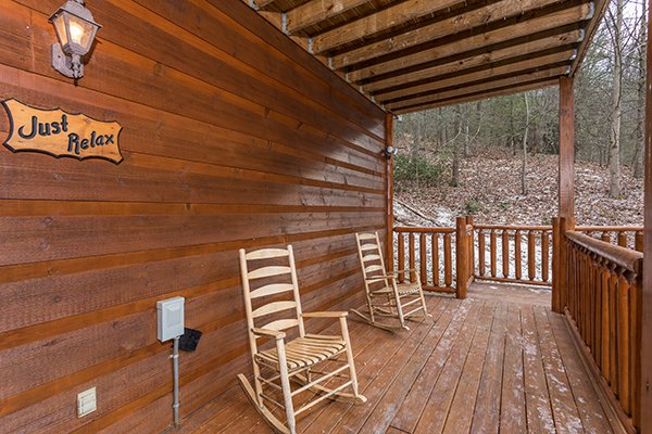 Rocking chairs on a covered deck surrounded by woods at Just Relax, a 2 bedroom cabin rental located in Pigeon Forge