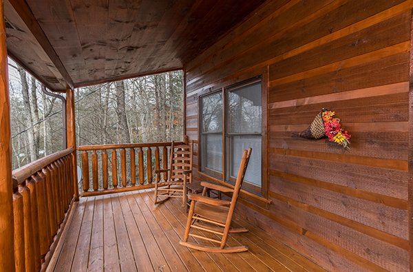 Rocking chairs on the covered deck at Just Relax, a 2 bedroom cabin rental located in Pigeon Forge