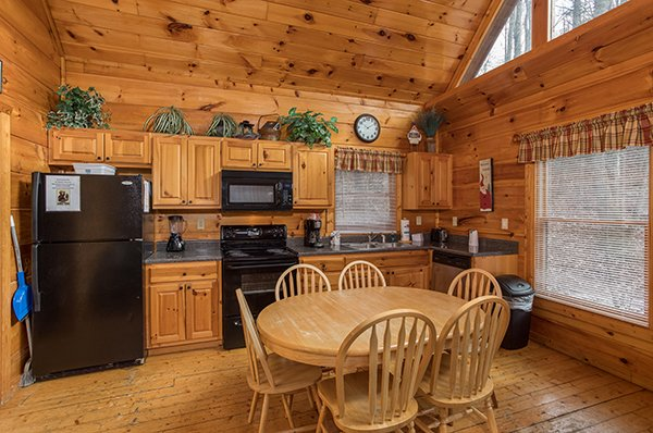 Dining table for six and kitchen with black appliances at Just Relax, a 2 bedroom cabin rental located in Pigeon Forge