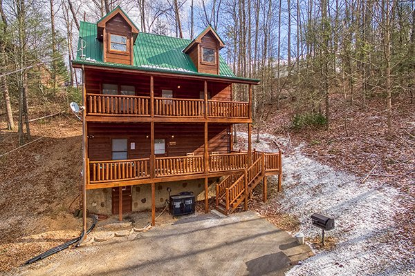 Cabin exterior surrounded by the woods and some snow at Just Relax, a 2 bedroom cabin rental located in Pigeon Forge