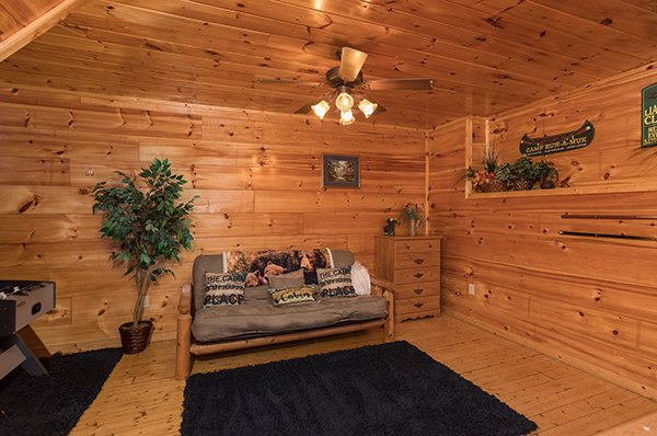 Futon and a dresser in the game room space at Just Relax, a 2 bedroom cabin rental located in Pigeon Forge