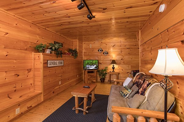Futon and television in the game room at Just Relax, a 2 bedroom cabin rental located in Pigeon Forge