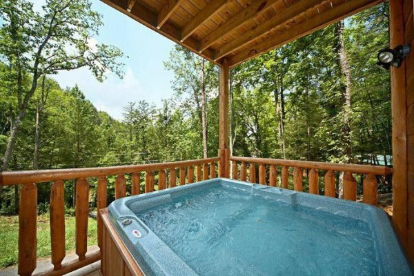 Hot tub on a covered deck at Just Relax, a 2 bedroom cabin rental located in Pigeon Forge