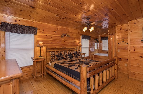 Bedroom with a king log bed and in room jacuzzi at Just Relax, a 2 bedroom cabin rental located in Pigeon Forge