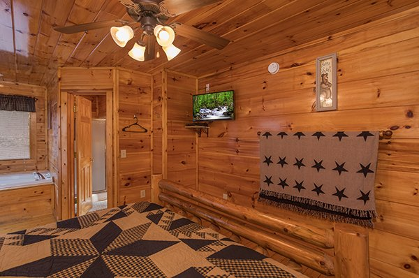 Bedroom with a TV and jacuzzi at Just Relax, a 2 bedroom cabin rental located in Pigeon Forge