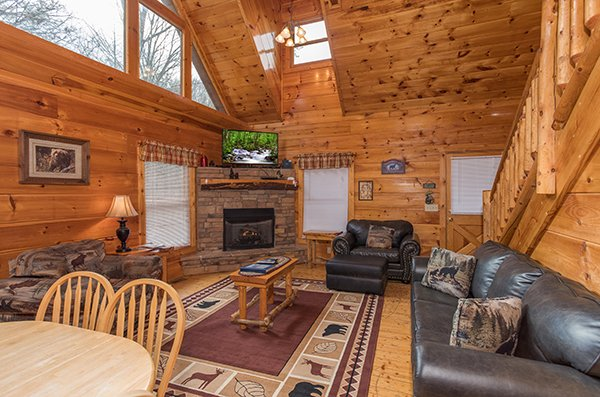 Living room with fireplace, TV, and an open concept floor plan at Just Relax, a 2 bedroom cabin rental located in Pigeon Forge