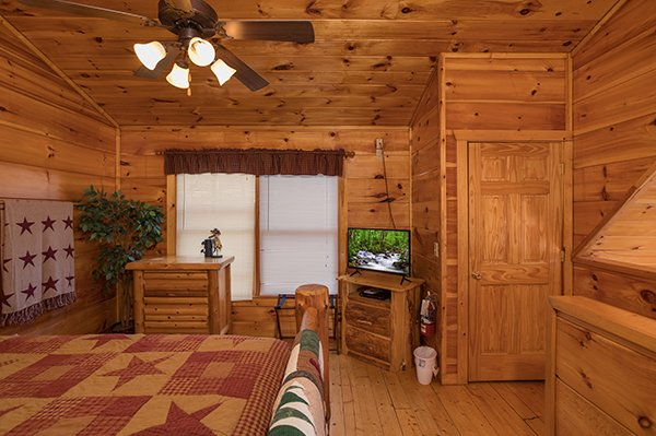Loft room with a dresser, TV, and laundry closet at Just Relax, a 2 bedroom cabin rental located in Pigeon Forge