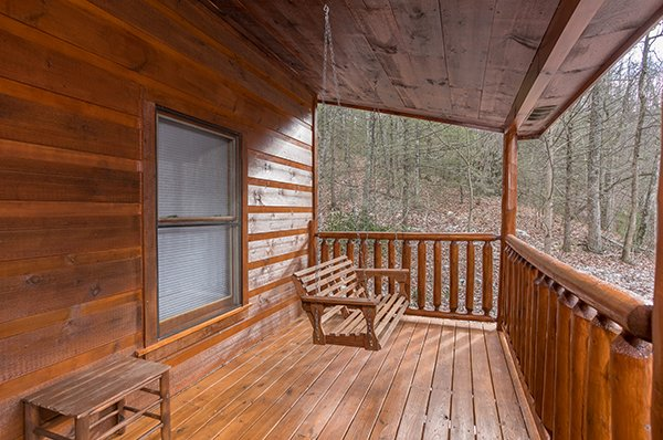Covered porch with a bench and swing surrounded by woods at Just Relax, a 2 bedroom cabin rental located in Pigeon Forge