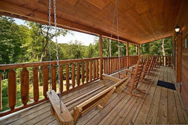 Covered porch with a swing and rocking chairs at Just Relax, a 2 bedroom cabin rental located in Pigeon Forge