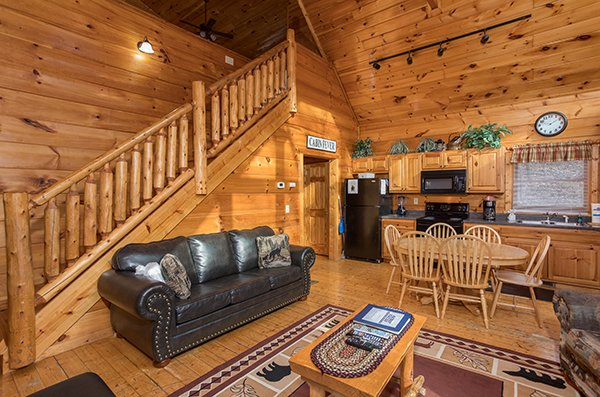 Sofa and dining room on the open concept main floor at Just Relax, a 2 bedroom cabin rental located in Pigeon Forge