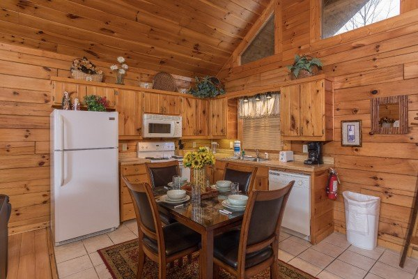 Dining space for four and kitchen with white appliances at Precious View, a 1 bedroom cabin rental located in Gatlinburg