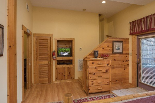 Dresser, closet, and TV in a bedroom with deck access at Precious View, a 1 bedroom cabin rental located in Gatlinburg