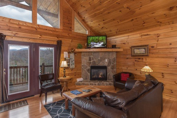 Living room with deck access, fireplace, and TV at Precious View, a 1 bedroom cabin rental located in Gatlinburg