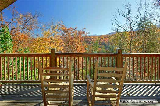 upper level deck with rockers and view of smoky mountains at precious view a 1 bedroom cabin rental located in gatlinburg