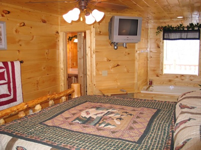 bathroom connected to bedroom with jacuzzi tub at hero's hideaway a 1 bedroom cabin rental located in gatlinburg