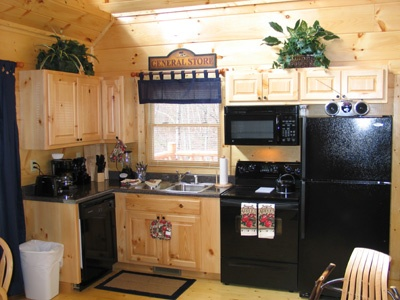 kitchen with black appliances at hero's hideaway a 1 bedroom cabin rental located in gatlinburg