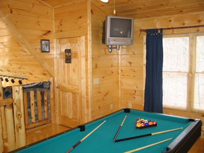 pool table and tv in lofted game room at hero's hideaway a 1 bedroom cabin rental located in gatlinburg