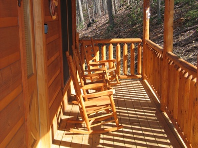 three rocking chairs on the front porch of hero's hideaway a 1 bedroom cabin rental located in gatlinburg