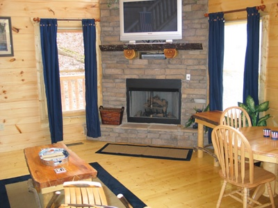 stone fireplace with tv above in living room of hero's hideaway a 1 bedroom cabin rental located in gatlinburg