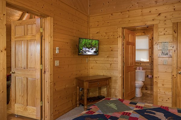 Console table and tv in a bedroom with an en suite at Southern Comfort Inn, a 4 bedroom cabin rental located in Pigeon Forge