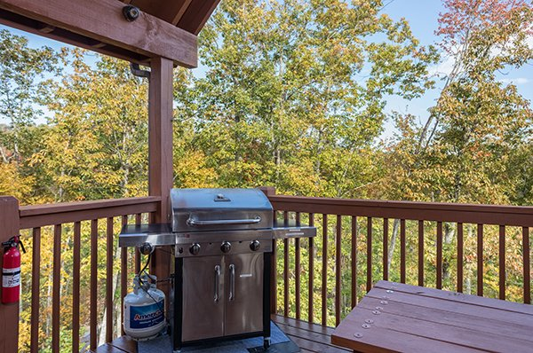 Propane grill on a covered deck at Southern Comfort Inn, a 4 bedroom cabin rental located in Pigeon Forge