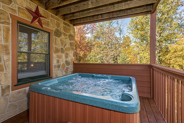 Hot tub on a covered deck at Southern Comfort Inn, a 4 bedroom cabin rental located in Pigeon Forge
