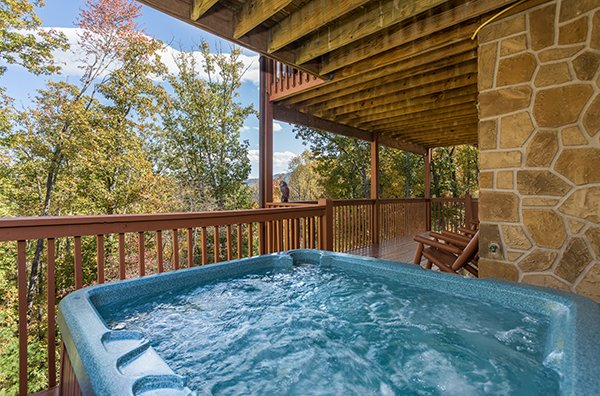 Hot tub on a covered deck with wooded views at Southern Comfort Inn, a 4 bedroom cabin rental located in Pigeon Forge