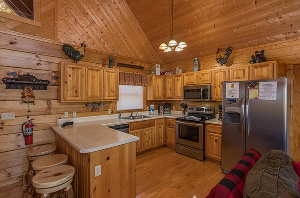 Kitchen with stainless appliances and counter seating for three at Southern Comfort Inn, a 4 bedroom cabin rental located in Pigeon Forge