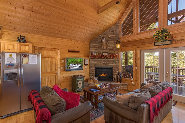 Living room with fireplace, TV, and deck access at Southern Comfort Inn, a 4 bedroom cabin rental located in Pigeon Forge