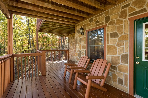 Lower deck with two log chairs at Southern Comfort Inn, a 4 bedroom cabin rental located in Pigeon Forge