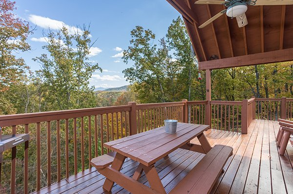 Picnic table on a covered deck at Southern Comfort Inn, a 4 bedroom cabin rental located in Pigeon Forge