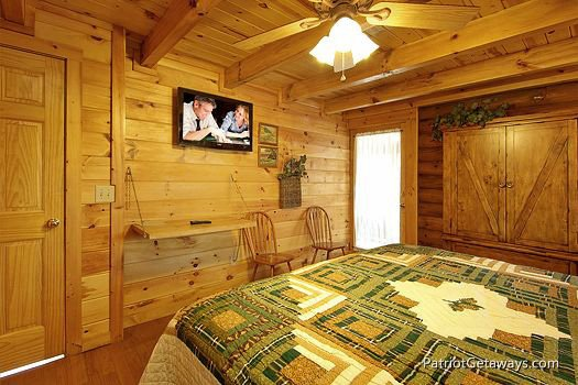 flat screen mounted tv in bedroom at a lover's secret a 1 bedroom cabin rental located in gatlinburg