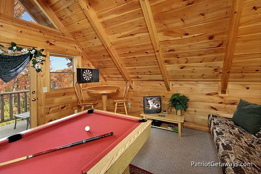 lofted game room with pool table and dart board along with a futon at a lover's secret a 1 bedroom cabin rental located in gatlinburg