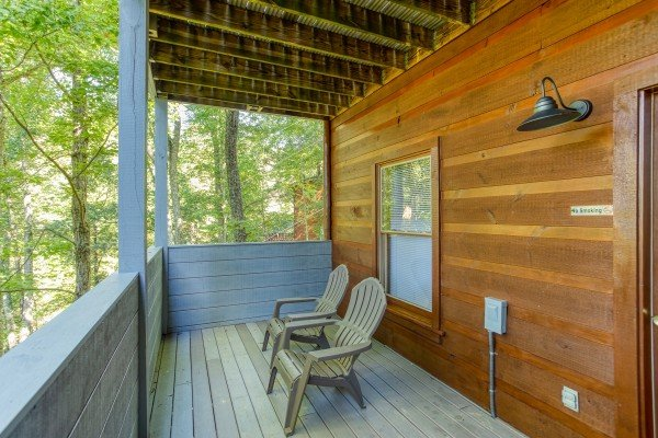 Covered deck with Adirondack chairs at Mountain Life, a 1 bedroom cabin rental located in Pigeon Forge