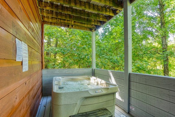 Hot tub on a covered deck at Mountain Life, a 1 bedroom cabin rental located in Pigeon Forge
