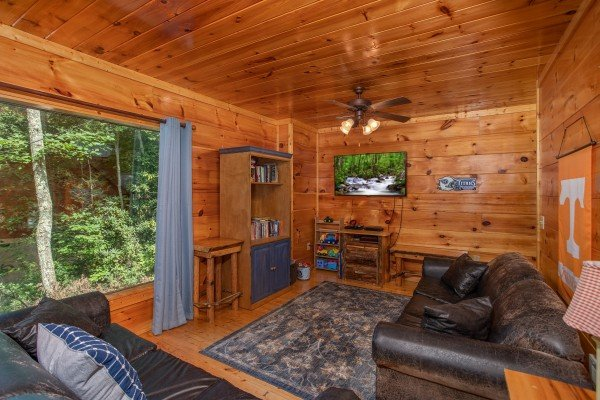 Living room on the lower level with a TV at Mountain Life, a 1 bedroom cabin rental located in Pigeon Forge