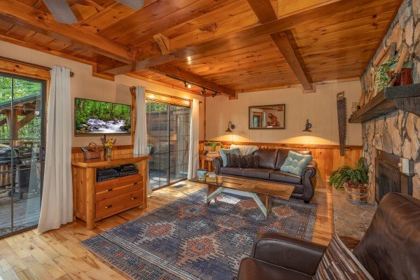 Living room with a TV and deck access at Hidden Pleasure, a 1-bedroom cabin rental located in Gatlinburg
