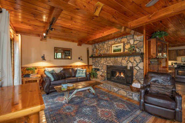 Fireplace, sofa, coffee table, and chair at Hidden Pleasure, a 1-bedroom cabin rental located in Gatlinburg