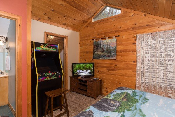 arcade game and television in the game room loft at a little slice of heaven a 1 bedroom cabin rental located in pigeon forge