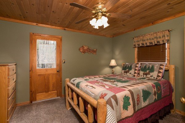 bedroom with log bed and deck access at a little slice of heaven a 1 bedroom cabin rental located in pigeon forge