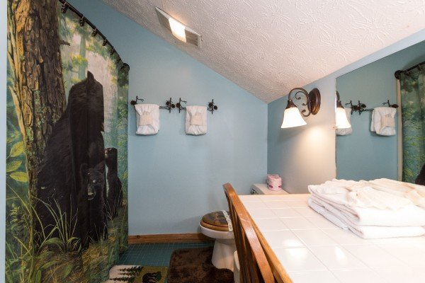 bathroom with bear decor at a little slice of heaven a 1 bedroom cabin rental located in pigeon forge
